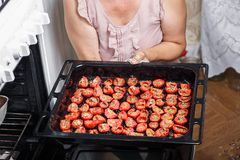 Housewife fry tomatoes Stock Image
