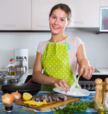 Housewife frying fish at kitchen Stock Photography