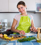 Housewife frying fish at kitchen Stock Image