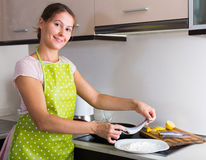 Housewife frying fish at kitchen Royalty Free Stock Images