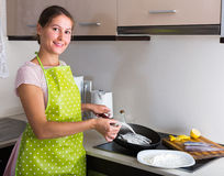Housewife frying fish at kitchen Stock Photos