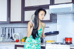 Housewife and frying pan Royalty Free Stock Images