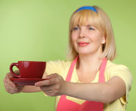 Housewife getting tea in red cap Stock Photography
