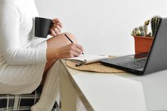 A housewife girl in a cozy white sweater and socks on a chair with a blanket works with a laptop in the kitchen. Online shopping a royalty free stock images