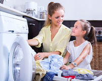 Housewife and girl doing laundry Stock Images