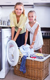 Housewife and girl doing laundry Stock Photos