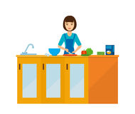 Housewife girl in the kitchen at the table, preparing food. Girl at home. A housewife girl in the kitchen at the table, preparing food, slicing food, against Stock Photos