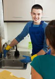 Housewife  in green watching plumber's work Stock Photography