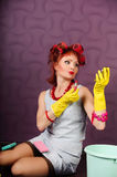 Housewife in hair curlers and rubber gloves paints lips lipstick Royalty Free Stock Images