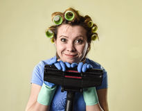 Housewife with hair rollers and gloves happy smiling cheerful holding vacuum cleaner. Young funny maid domestic service woman or housewife with hair rollers and Stock Photo