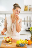 Housewife having a bite while making fruit salad in kitchen Stock Image