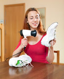 Housewife heating sneakers hairdryer Stock Photo