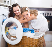 Housewife and her daughter with linen near washing machine Royalty Free Stock Photos