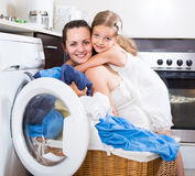 Housewife and her daughter with linen near washing machine Royalty Free Stock Images