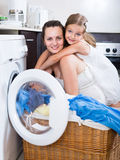 Housewife and her daughter with linen near washing machine Stock Photography