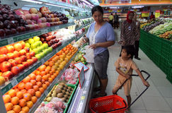 Housewife and her son shopping at one of the supermarkets in the city of Solo, Central Java Indonesia. they buy fruit and other ba. Sic necessities, supermarket Stock Photos