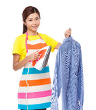 Housewife hold of iron steamer with blue shirt Royalty Free Stock Photography