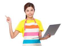 Housewife hold with laptop computer and finger point up Stock Image