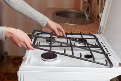 Housewife hold metal grates to clean the dirty kitchen gas stove. Housewife hold metal grates to clean the dirty kitchen gas stove stock photo
