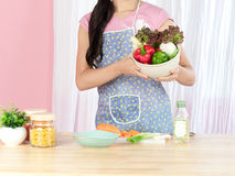 A housewife holding a bowl of vegetables Stock Image