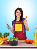 Housewife holding carrot Royalty Free Stock Photography