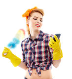Housewife holding a duster and looking at a mobile phone Royalty Free Stock Photos