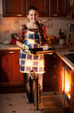 Housewife holding form with chocolate cookies near oven Royalty Free Stock Photo