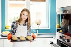 Housewife holding hot roasting pan with  freshly baked bread rolls. Stock Image