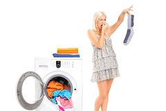 A housewife holding a male sock and her nose Stock Photos