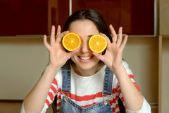 Housewife holding orange slices in front of her eyes and smiles Royalty Free Stock Photos
