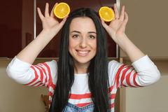 Housewife holding orange slices over her head and having fun Stock Photography