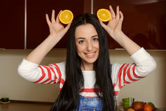 Housewife holding orange slices over her head and laughs Stock Image