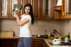 Housewife holding a pan. It stands in the kitchen Stock Images