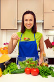 Housewife holding spoon with salad Royalty Free Stock Images
