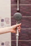 Housewife holds in her hand cleen and сlosed off rain shower head in the bathroom Stock Photos