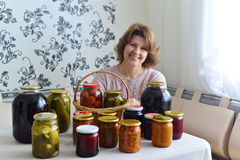 housewife with home canned vegetables in room Royalty Free Stock Photo