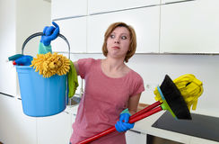 Housewife at home kitchen in gloves holding cleaning broom and mop and bucket Royalty Free Stock Photography