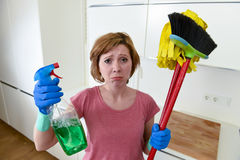 Housewife at home kitchen in gloves holding cleaning broom and mop and spray bottle Royalty Free Stock Photography