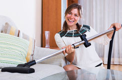 Housewife hoovering surfaces at home Royalty Free Stock Photography
