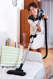 Housewife hoovering surfaces at home Stock Photo