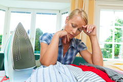 Housewife with iron. A young housewife with iron during ironing and laundry Stock Photo