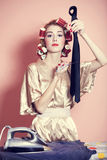 Housewife with iron and curler royalty free stock photography