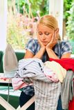 Housewife with iron during ironing and laundry. A young housewife with iron and ironing clothes Stock Image