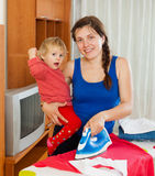 Housewife ironing clothes on the ironing board Stock Photos