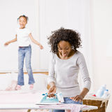 Housewife ironing laundry while girl jumps on bed Stock Images