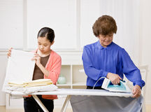 Housewife ironing laundry with granddaughter Stock Photo