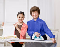 Housewife ironing laundry with granddaughter Stock Photos