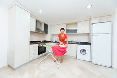 Housewife ironing laundry in kitchen Stock Photos