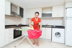 Housewife ironing laundry in middle of the kitchen Royalty Free Stock Photo