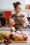 Housewife with jars of pickled vegetables Stock Images